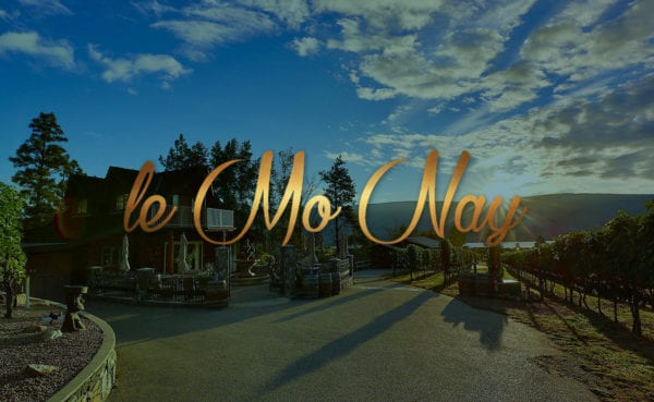"""title """"le mo nay"""" with an orchard and winery displayed in the background"""