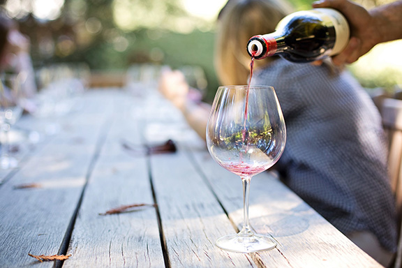 Summerland winery picnic table with an empty wine glass and wine bottle pouring into it